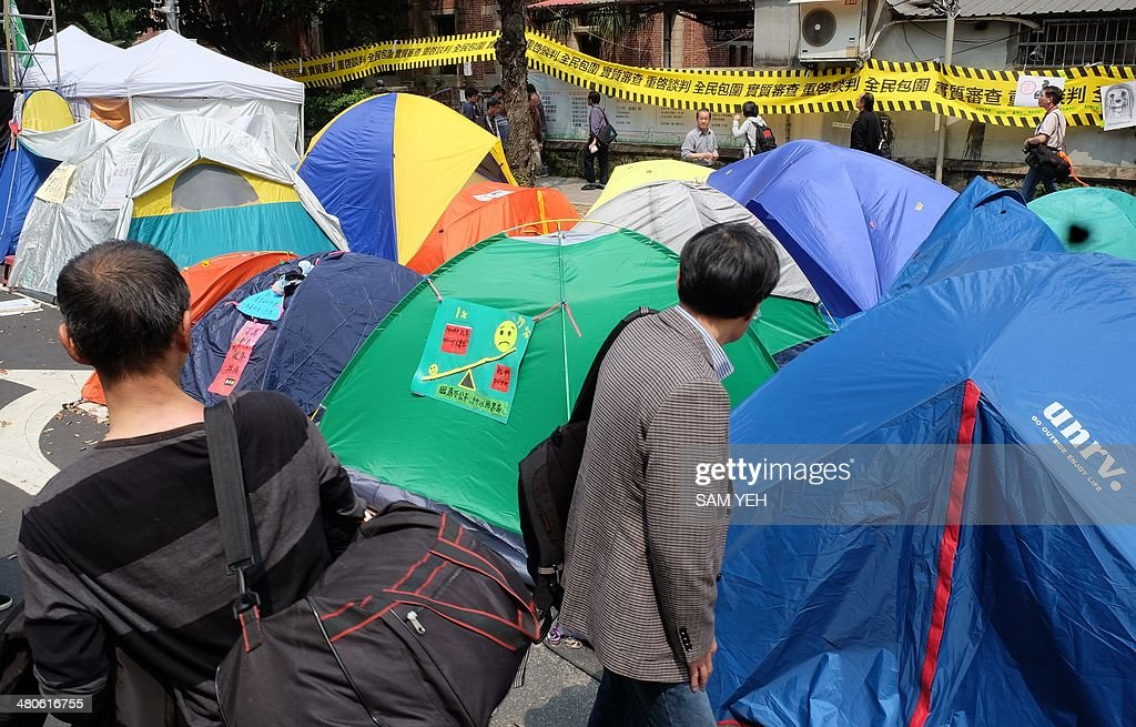 Local residents walk past tents as student protesters occupy the streets outside of Parliament in Taipei on March 26, 2014. Taiwan's President Ma offered to talk with the protesters in a concession to student demonstrators who have occupied parliament for the past week in a bid to stop the government from ratifying a contentious trade agreement with China. AFP PHOTO / Sam Yeh
