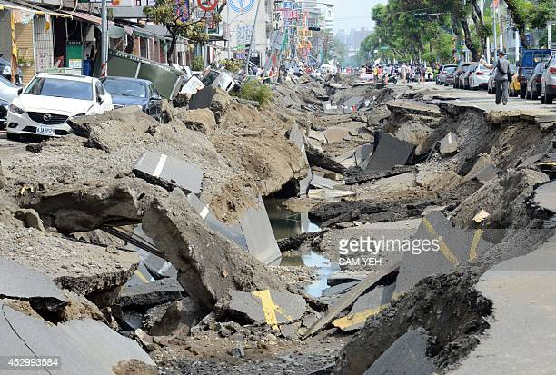 Local residents walk past the gas explosion site in the southern Taiwan city of Kaohsiung on August 1 2014 A series of powerful gas blasts killed at...