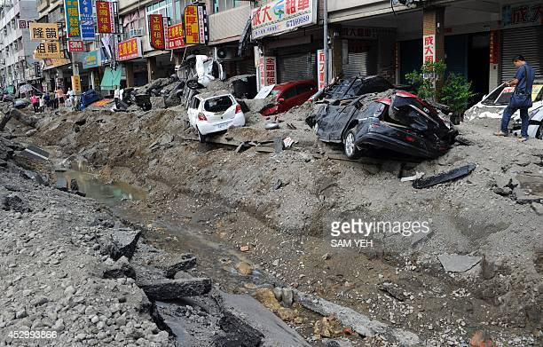 Local residents walk past the site of a gas explosion in the southern Taiwan city of Kaohsiung on August 1 2014 A series of powerful gas blasts...