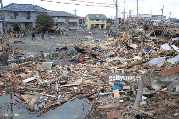 Local residents walk through an area damaged by tsunami after a 90 magnitude strong earthquake struck on March 11 off the coast of northeastern Japan...