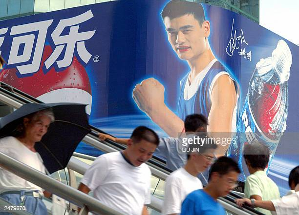 Local residents walks before a huge billboard of American giant beverage company Pepsi showing NBA Houston Rocket's player Yao Ming in Shanghai 04...