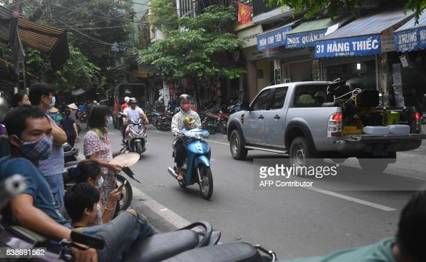 Local residents watch an official pickup truck transporting a sprayingmachine on its back along a Hanoi street to spray mostiquokilling chemical as...