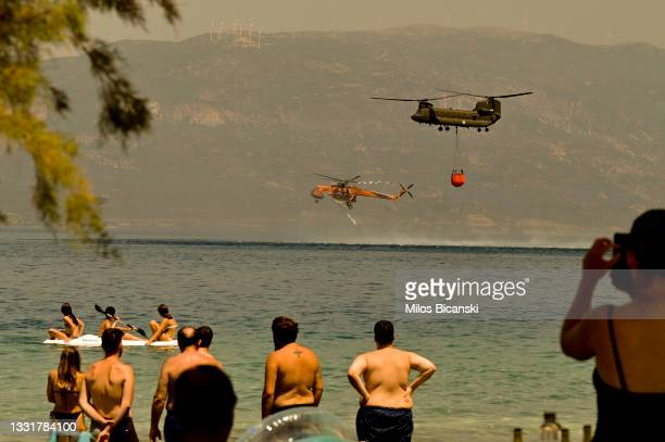 Local residents watch as a Greek army Chinook helicopter and a Sikorsky S-64 Skycrane helicopter collect water as firefighters continue to tackle a...