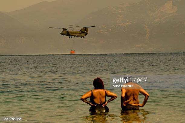 Local residents watch as a Greek army Chinook helicopter collects water as firefighters continue to tackle a wildfire near the village of Lambiri on...