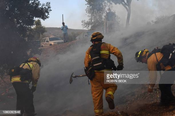 Local residents watch as firefighters work to control a flare up due to flying embers from the Woolsey Fire November 10 2018 in Calabasas California...