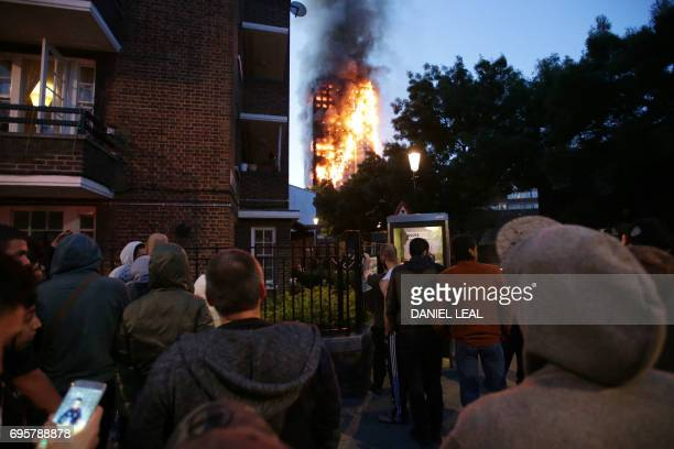 TOPSHOT Local residents watch as Grenfell Tower is engulfed by fire on June 14 2017 in west London The massive fire ripped through the 27storey...
