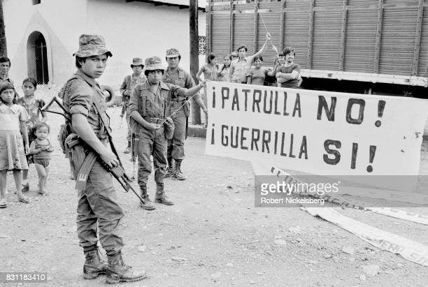 Local residents watch as Guatemalan army soldiers show captured banners made by a militant guerrilla group October 1 1982 in Huehuetenango Guatemala...