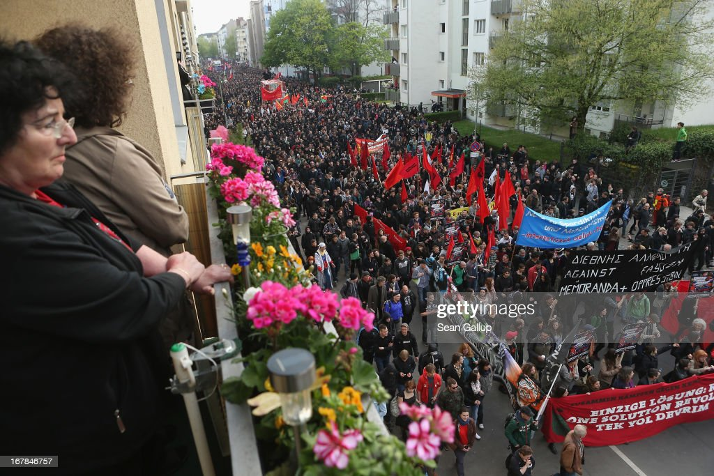 "Local residents watch as left-wing protesters march in the annual ""Revolutionaerer 1. Mai"" (Revolutionary May 1st) demonstration in Kreuzberg district on May Day on May 1, 2103 in Berlin, Germany. Several thousand protesters took part in the march that in years past has been plagued by violent clashes between marchers and police."