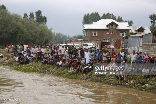 Local residents watch as state Disaster Response Force personnel search for the body of man who went missing during flash floods at Tailbal on July...