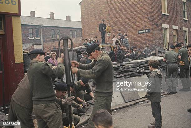Local residents watch British troops and soldiers erecting barricades on the corner of Lucknow street located between the predominantly Catholic...