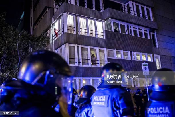 Local residents watch from their apartments as Mossos d'Esquadra police officers control the route of rival antifascists and fascist demonstrations...