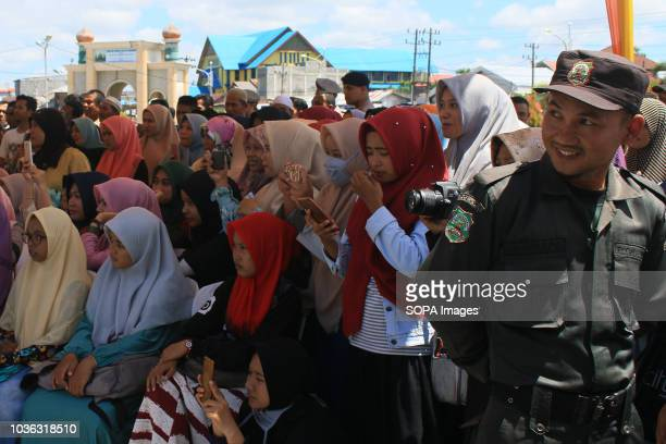 Local residents watch the prisoners got whipped 19 people were sentenced by the Meulaboh Sharia Court to being whipped in public for sexually abusing...