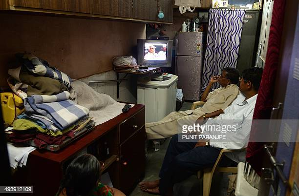 Local residents watch the swearingin ceremony for Indian prime ministerdesignate Narendra Modi on a television in the Dharavi slum area in Mumbai on...