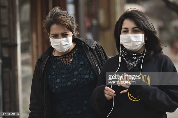 Local residents wear masks to protect themselves from the ashes spewed by the 400-kilometre distant Calbuco volcano in Pucon, southern Chile, on...