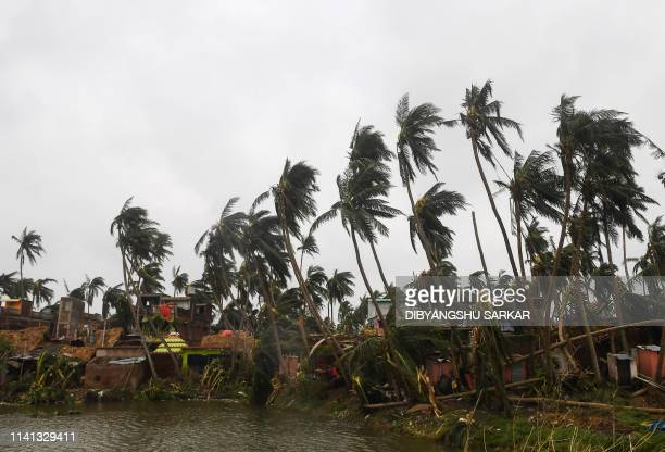 Local residents work to clear away debris next to broken palm trees in Puri on May 5 after Cyclone Fani swept through the area Cyclone Fani one of...