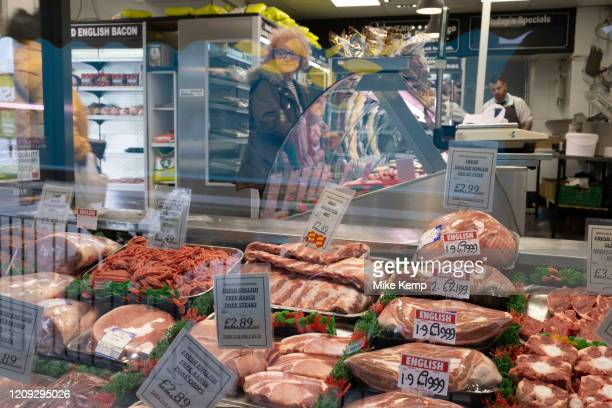 Local response to Coronavirus is felt on a street by street level as the butcher on Kings Heath High Street is still trading on 6th April 2020 in...