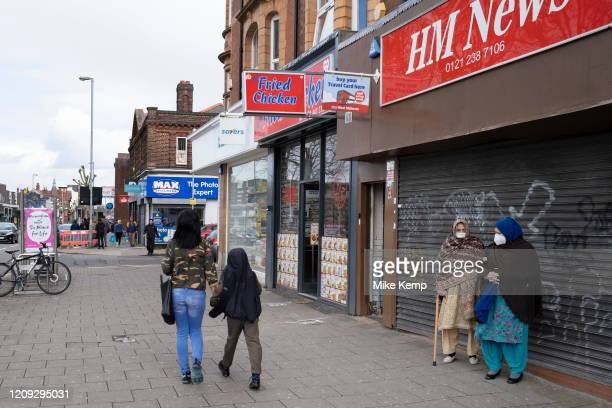 Local response to Coronavirus is felt on a street by street level as People wearing face masks go about their day to day shopping on Kings Heath High...