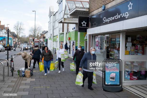 Local response to Coronavirus is felt on a street by street level as people wearing face masks carry their shopping bags outside Asda supermarket on...