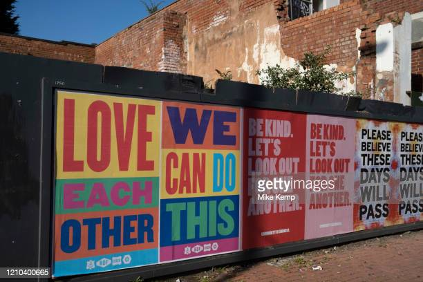 Local response to Coronavirus is felt on a street by street level as posters are pasted up on a hoarding promoting community love and belief,...