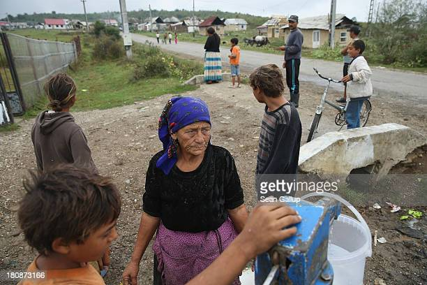 Local Roma residents collect water from the single community well in the abjectly poor Roma settlement of Ponorata on September 10 2013 in Ponorata...