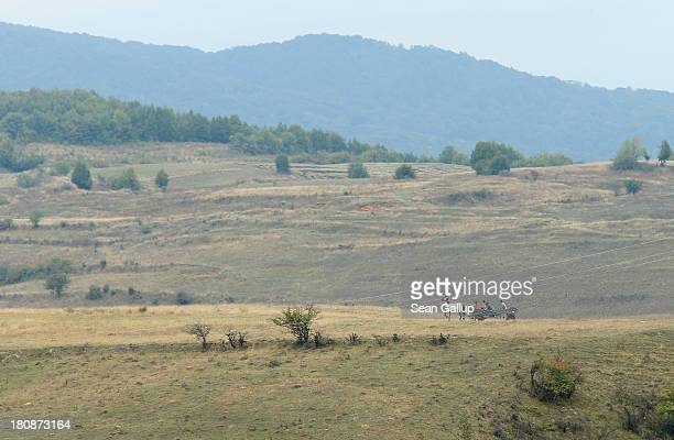 Local Roma residents ride a horsedrawn cart across a field near the abjectly poor Roma settlement of Ponorata on September 10 2013 in Ponorata...