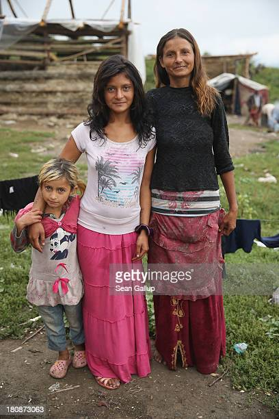 Local Roma sisters Smocina Boldis and Marinela Boldis along with Angela Varga pose for a photo in the abjectly poor Roma settlement of Ponorata on...