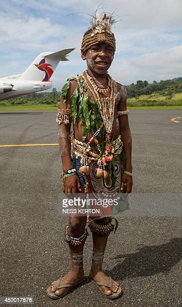 A local school boy in traditional dress greets Japan's Prime Minister Shinzo Abe at the airport in Wewak in Papua New Guinea on July 11 2014 Abe is...