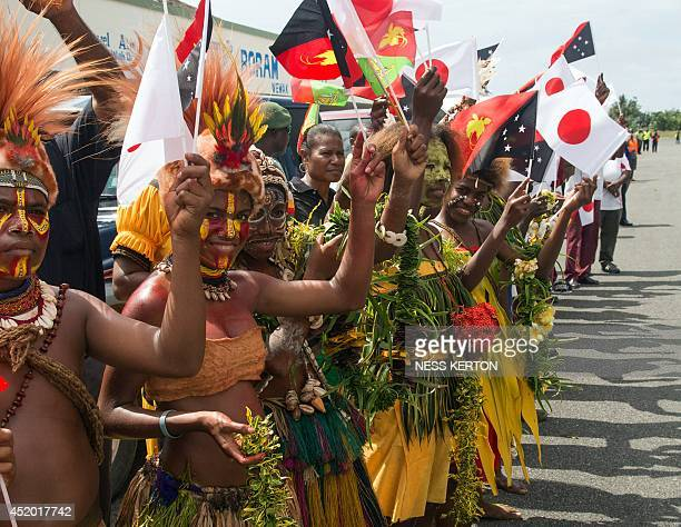 Local school children in traditional dress greet Japan's Prime Minister Shinzo Abe at the airport in Wewak in Papua New Guinea on July 11 2014 Abe is...