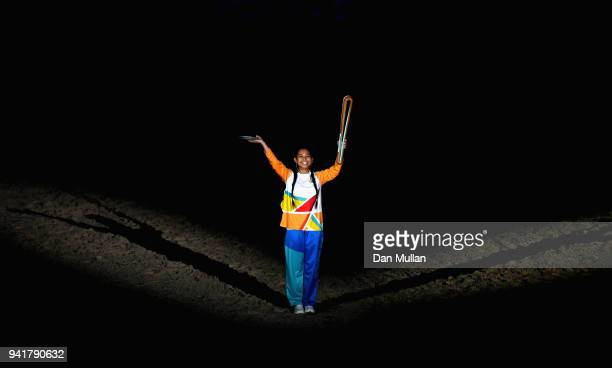 A local school girl is presented with The Queen's Baton during the Opening Ceremony for the Gold Coast 2018 Commonwealth Games at Carrara Stadium on...