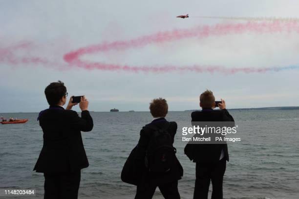 Local schoolchildren take pictures of the Red Arrow display over Portsmouth during the commemorations for the 75th anniversary of the DDay landings