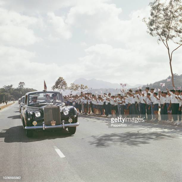 Local schoolchildren wave union flags beside a road as a motorcade, headed by Princess Alexandra's Rolls Royce car, drives past during a royal tour...