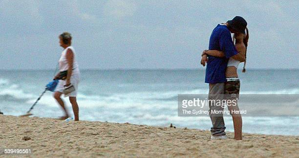 A local searching for treasures as a young schoolie couple embrace on Main Beach during Schoolies week in Queensland's Surfers Paradise 21 November...