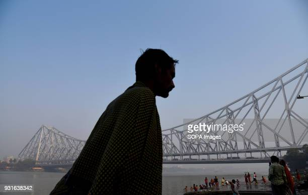 A local seen walking in front of the Howrah bridge in Kolkata The Rabindra Setu also known as the Howrah bridge is a bridge with a suspended span...