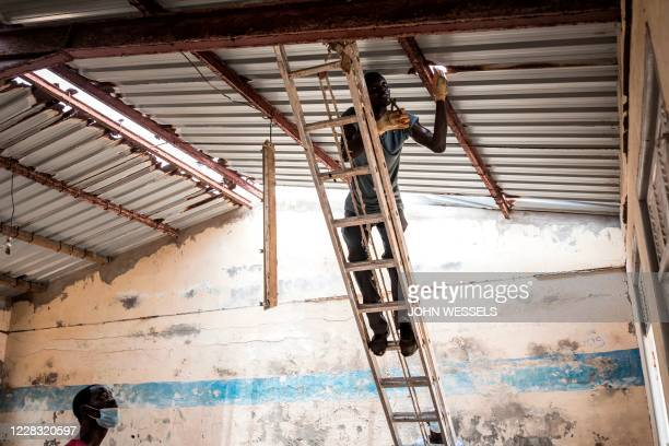 Local Senegalese activists fix a broken roof at Yoff high school in Dakar on August 29, 2020. - These classrooms, which are without electricity and...