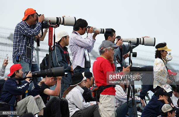 Local spectators take photographs from the stands during practice for the Japanese Formula One Grand Prix at the Fuji Speedway on October 10 2008 in...