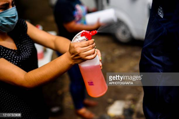 A local sprays a person with chemicals to allowed to enter into the town of El Rosario during government issued lockdown on May 18 2020 in Cuscatlan...