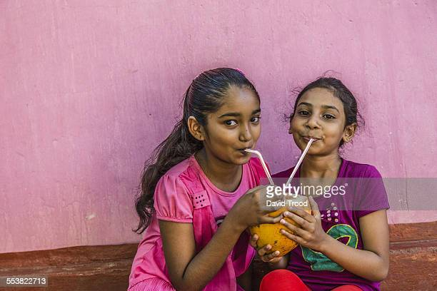 Local Sri Lankan girls drink from a fresh coconut.