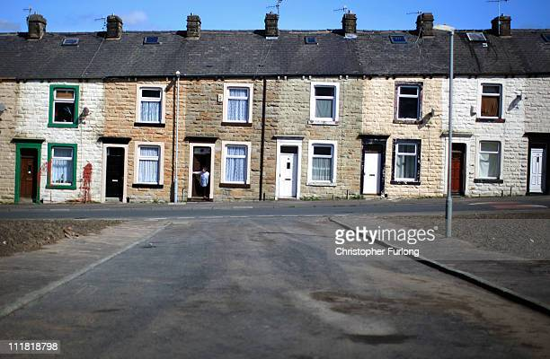 Local stands in the doorway of their home in a terraced street in Burnley, Lancashire, which is the cheapest place in England and Wales to buy a...