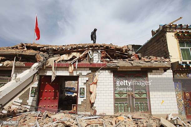 Local stands on the roof of a partly collapsed building and observes the surrounding damage from an earthquake on April 16, 2010 in Golmud, China. It...
