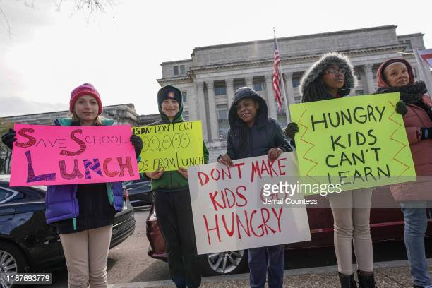 Local students hold signs at a press conference organized to deliver 1.5 million petitions to the USDA to Save School Lunch on November 14, 2019 in...