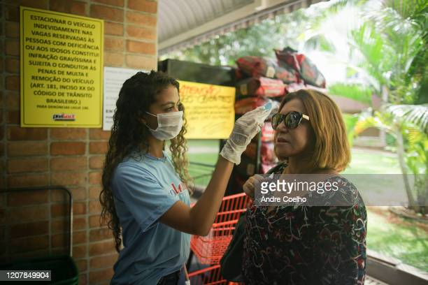 Local supermarket employee checks the temperature of clients as the coronavirus continues to Spread in Brazil, on March 20, 2020 in Brasilia, Brazil....