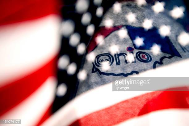 A local supporter holds an American flag in front of the Ohio logo on his shirt as he stood with a crowd at Shawnee State University to hear...