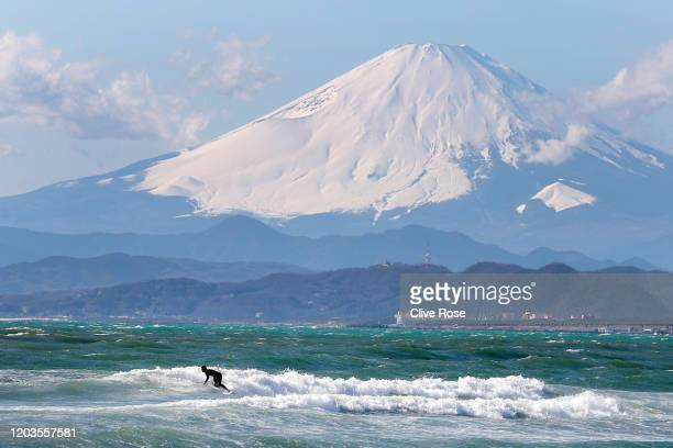 Local surfer is seen in action with Mount Fuji in the background from the beach of Enoshima during the build up to the Tokyo 2020 Olympic Games on...