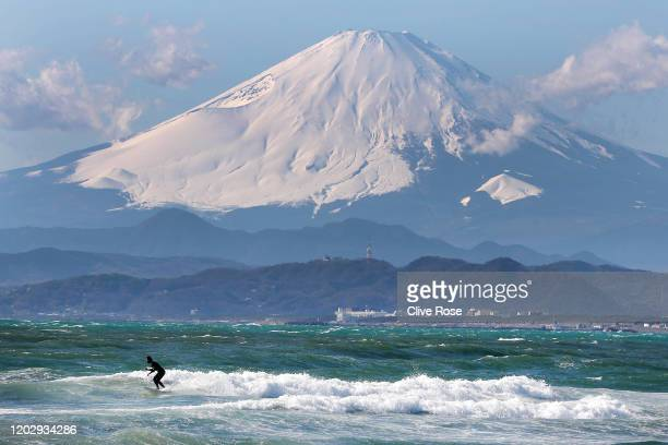 Local surfer is seen with Mount Fuji in the background from the beach of Enoshima during the build up to the Tokyo 2020 Olympic Games on January 30,...