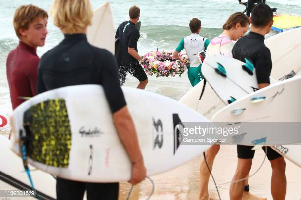 Local surfers and surfers competing in the Sydney Surf Pro participate in a paddleout wreath laying and observe a minute of silence to remember...