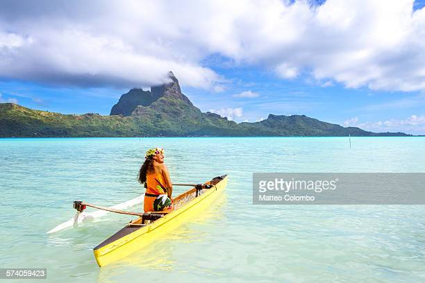 Local tahitian woman in outrigger canoe, Bora Bora