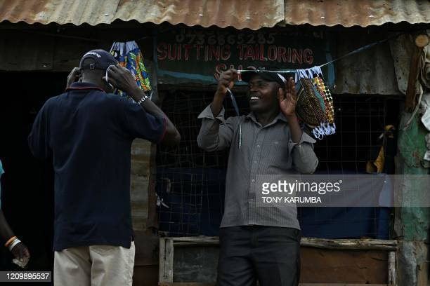 A local tailor sells face masks he made from cloth outside his shop in the Kibera slum Nairobi on April 14 2020 Kenya has so far cordoned off the...