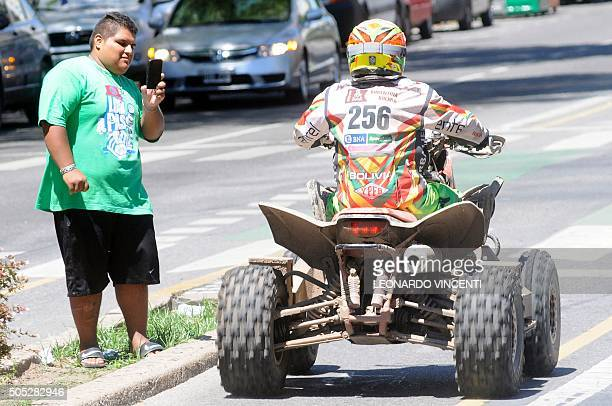 A local takes a picture of Bolivian quad driver Walter Nosiglia after at the end of Stage 13 of the Rally Dakar 2016 between Villa Carlos Paz and...