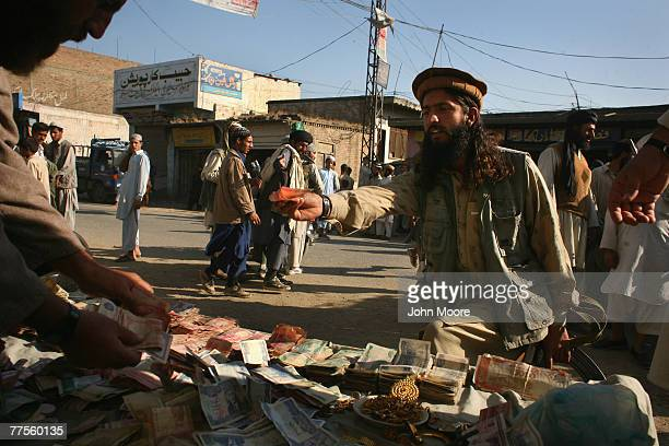 A local Taliban militant contributes at a donation table for mujahideen in the village of Koza Bandi October 30 2007 in the Swat Valley of Pakistan...