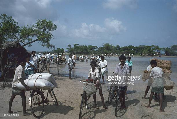 Local Tamil residents push bicycles to cross a lagoon October 1, 1998 to and from Batticaloa and Jaffna in Kokkadichcholai, Sri Lanka. Vehicular...